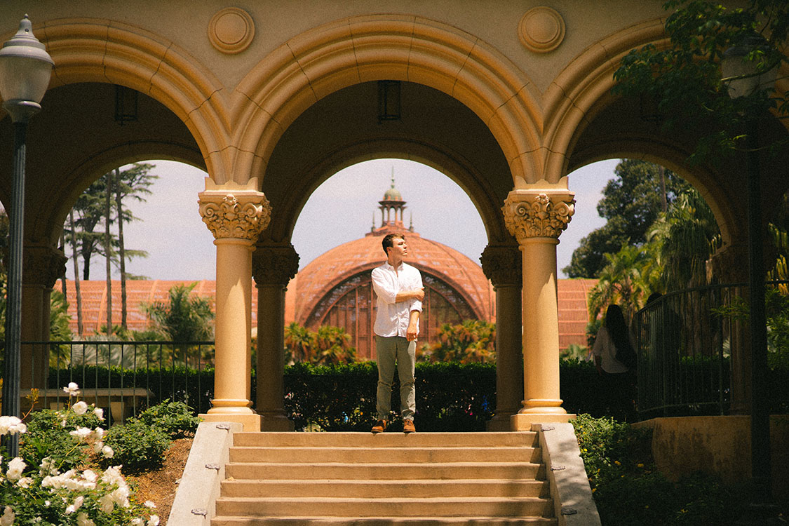 Man in white button-up shirt stands under Spanish archway at top of stairs