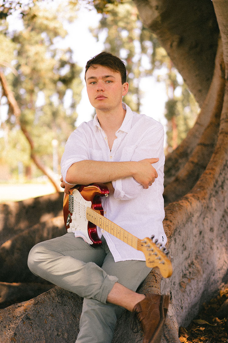 Man in white button-up shirt sits on a Moreton Bay fig tree with his electric guitar