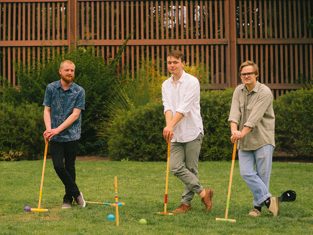 Three men play croquet in front of the Balboa Park Botanical Garden
