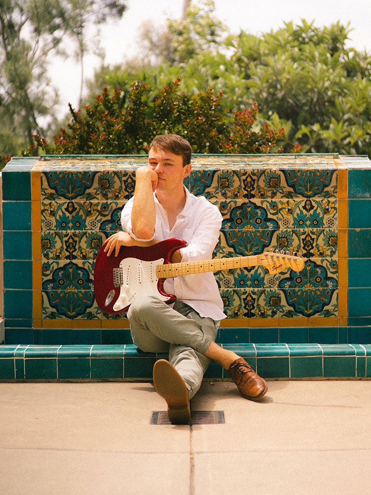 Man in white button-up shirt sits with electric guitar in front of a Spanish tile fountain