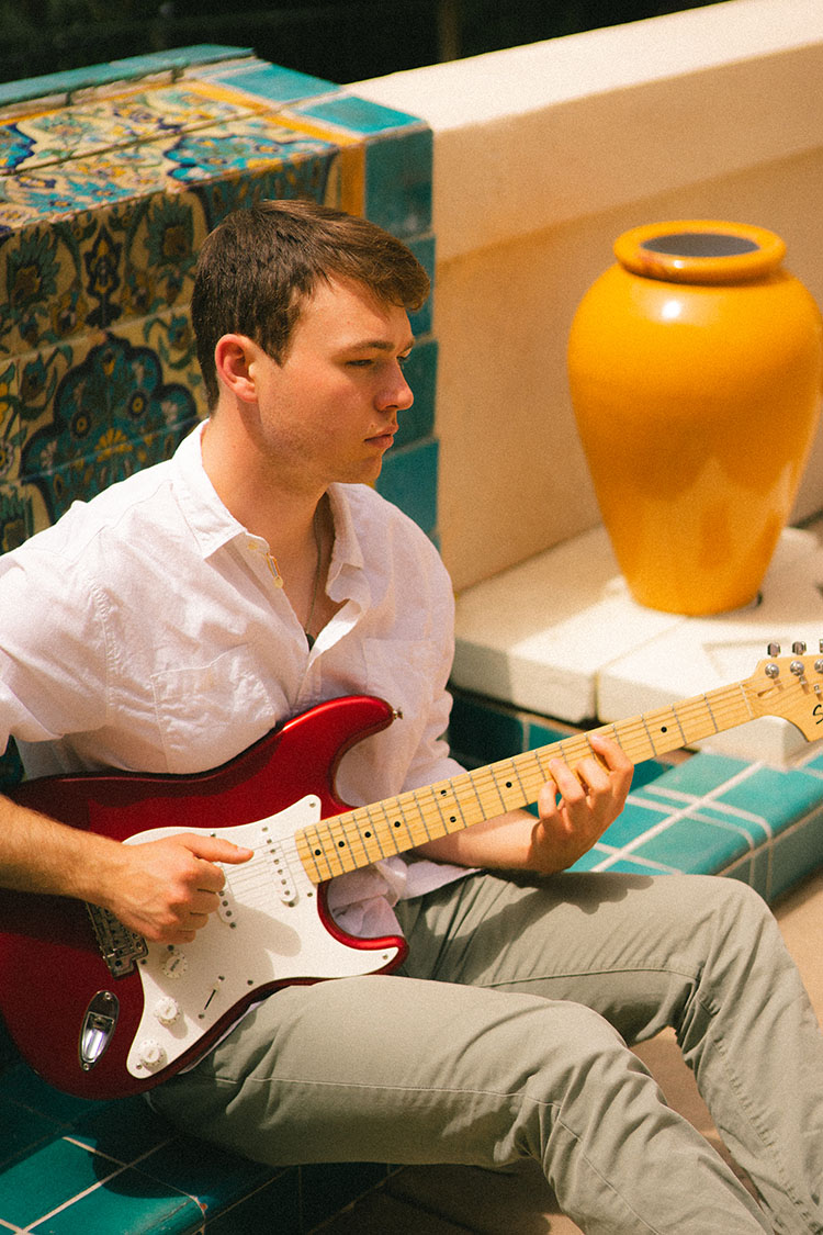 Man in white button-up shirt plays electric guitar in front of a Spanish tile fountain
